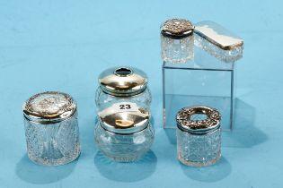 AN EDWARDIAN CYLINDRICAL CUT GLASS TOILET JAR with silver cherub head design lid, Birmingham 1906, a