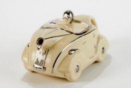 AN ART DECO CREAM GLAZED POTTERY RACING CAR TEAPOT with silvered decoration and registration plate
