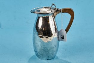 A GEORGE V SILVER ARTS AND CRAFTS INFLUENCE HOT WATER JUG, spot hammered with tendril thumb piece,