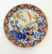 An Oriental plate in the Imari palette decorated with flowers, foliage and an Asiatic pheasant.