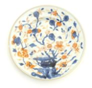 A Japanese plate in the Imari palette with hand painted decoration depicting blossoming flowers.