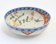 A Japanese bowl with hand painted decoration depicting a landscape scene with flowers, a crane