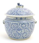 A Chinese blue and white pot and cover with scrolling floral and foliate detail. The lid
