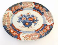 A Japanese Imari style plate, the centre decorated with a vase of flowers with a floral border.