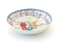 An Oriental famille rose dish depicting a mountainous landscape scene with two figures and a child