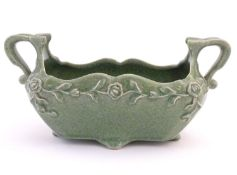 A celadon style plant holder / flower trough with a crackle glaze and floral and foliate detail.