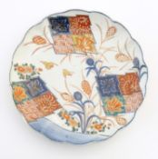 A Japanese plate with a lobed rim, hand painted in the Imari palette with stylised flowers and