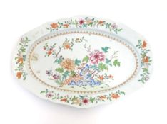 A Chinese famille rose oval dish with hand painted floral and foliate detail, with peonies and