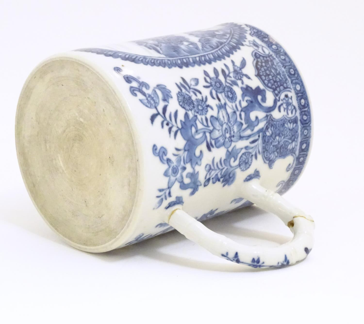 A Chinese blue and white export mug depicting a landscape scene with pagodas, with floral and - Image 2 of 6