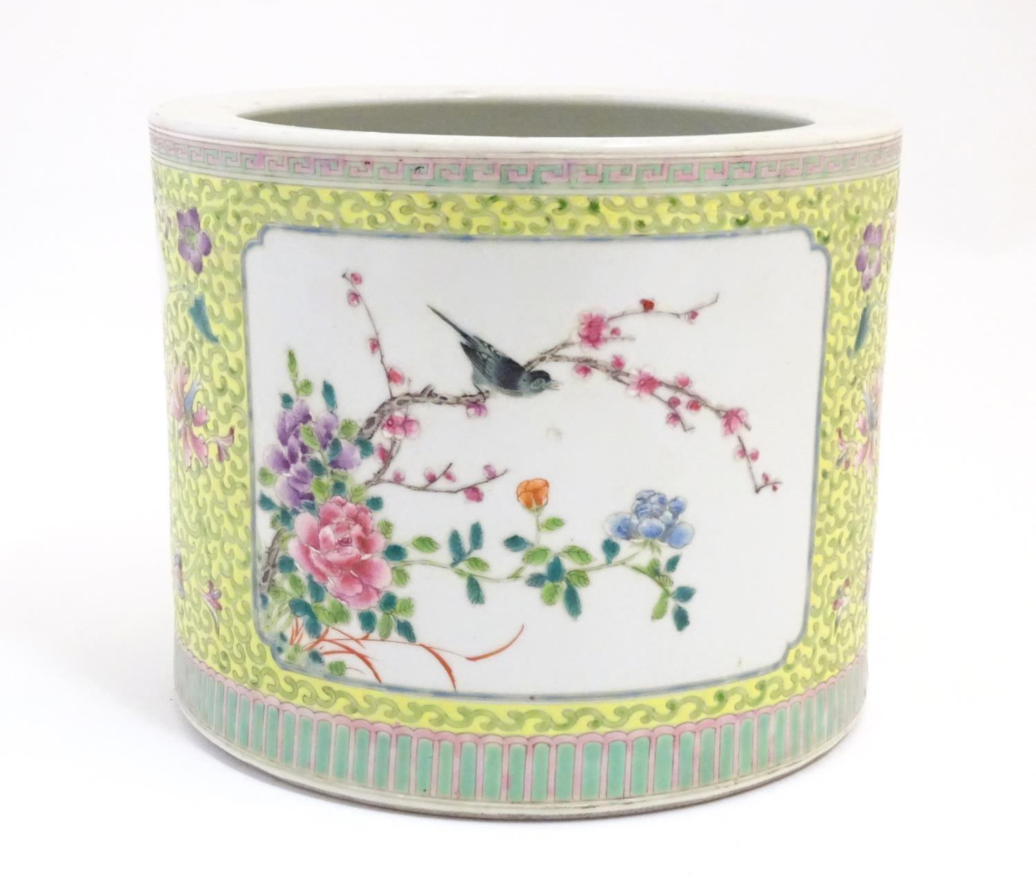 A Chinese famille jaune planter with a floral and foliate ground and panelled decoration with