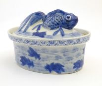 A Chinese blue and white dish and cover of oval form, the lid surmounted by a fish in relief, the