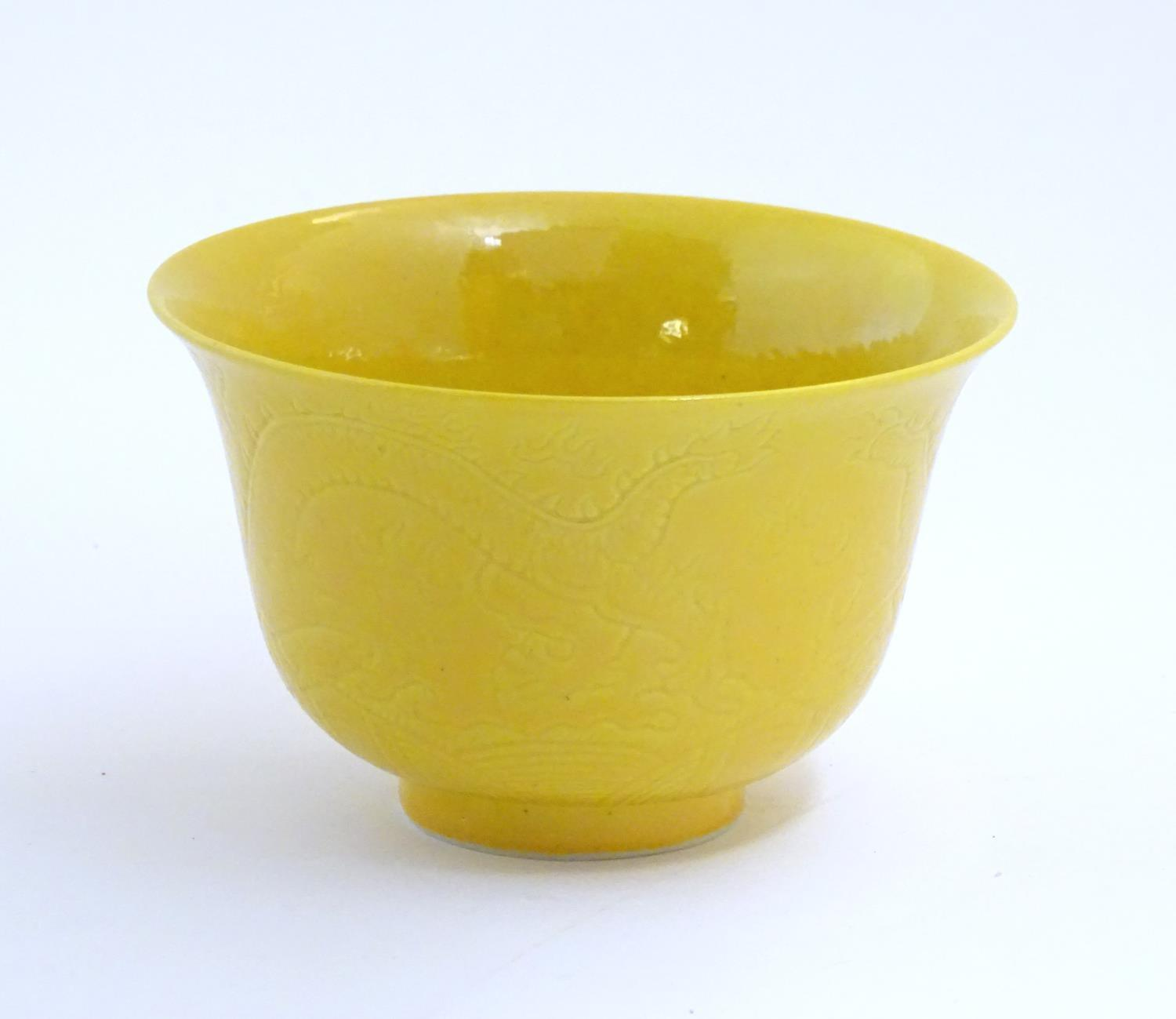 A Chinese dragon bowl with a yellow ground with incised decoration depicting dragons and stylised
