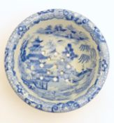 A 19thC blue and white small strainer, decorated with an Oriental landscape scene with pagodas