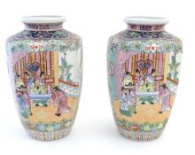 A pair of Oriental vases with panelled decoration depicting an interior scene with an Imperial