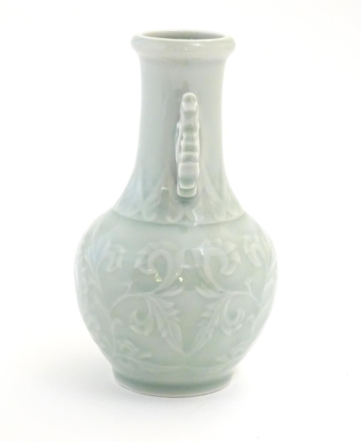 A Chinese celadon green baluster vase with twin handles and stylised foliate design. Approx. 6 1/ - Image 4 of 6