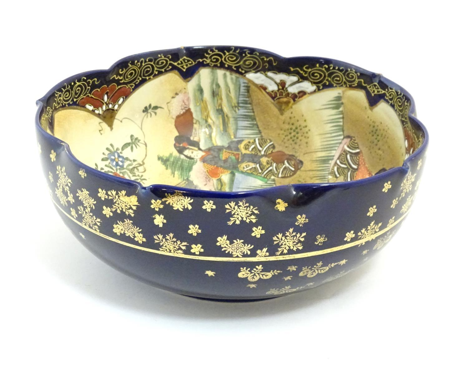 A Japanese export bowl with a lobed rim, decorated with Geisha girls with fans and flowers in a