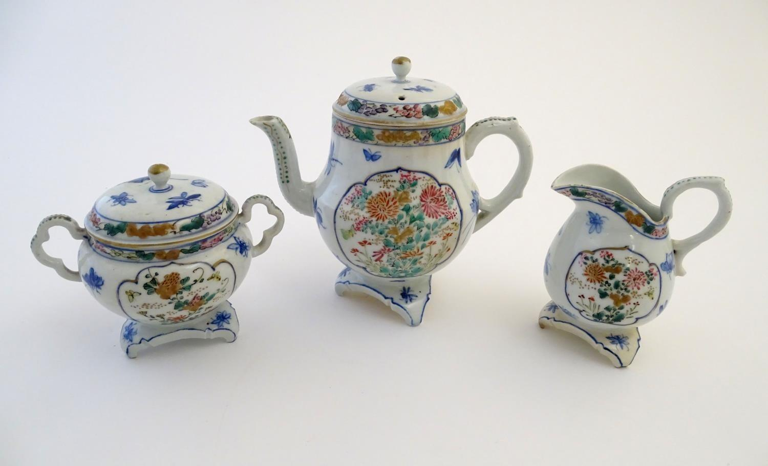 A Japanese teapot, twin handled sugar bowl and milk jug decorated with hand painted insects and