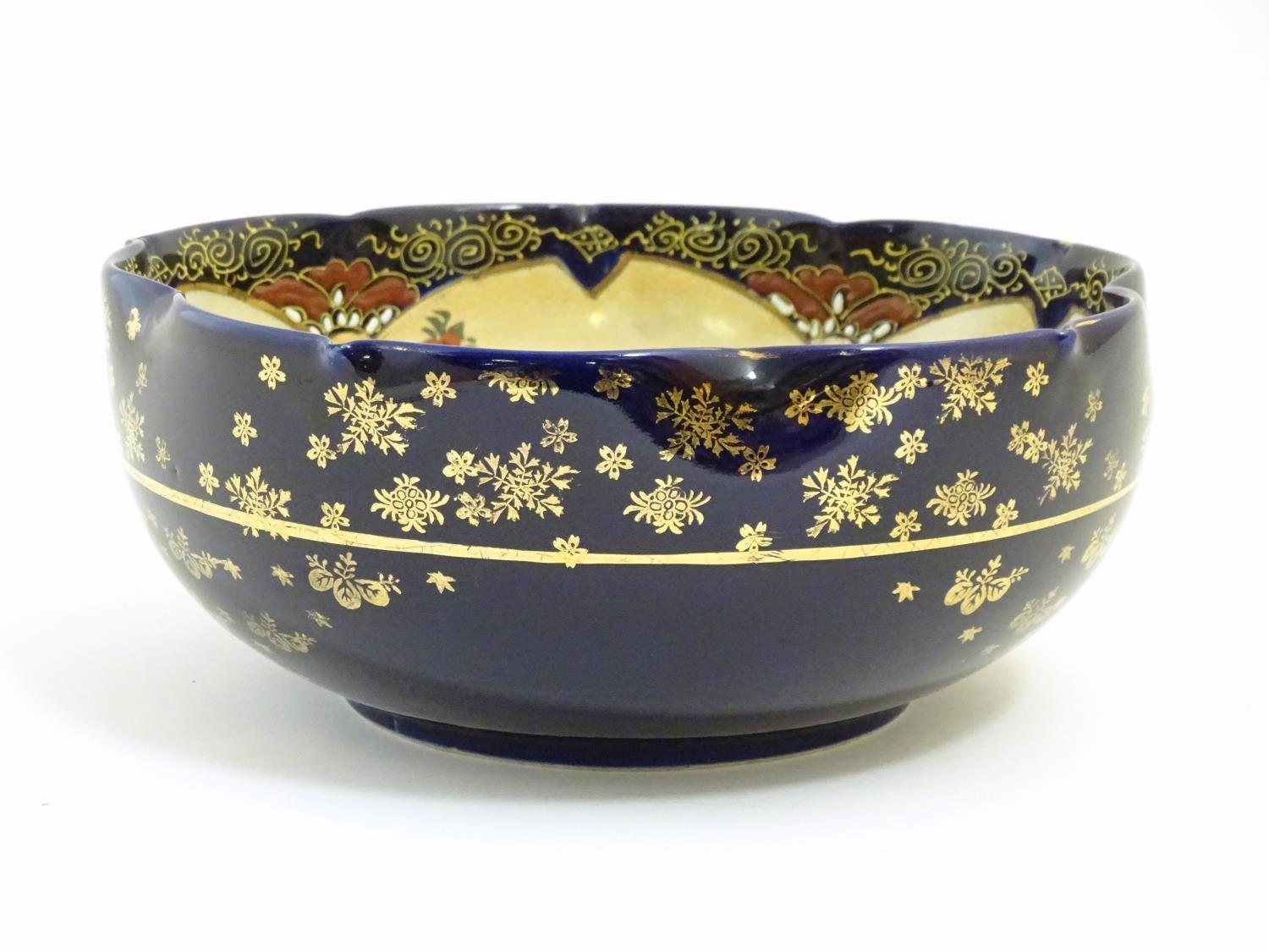 A Japanese export bowl with a lobed rim, decorated with Geisha girls with fans and flowers in a - Image 2 of 7