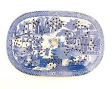 An English blue and white strainer with chinoiserie decoration depicting a fishing village with