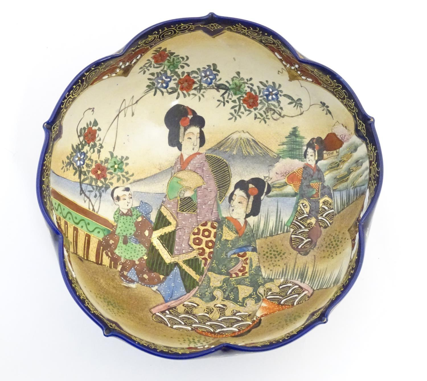 A Japanese export bowl with a lobed rim, decorated with Geisha girls with fans and flowers in a - Image 3 of 7