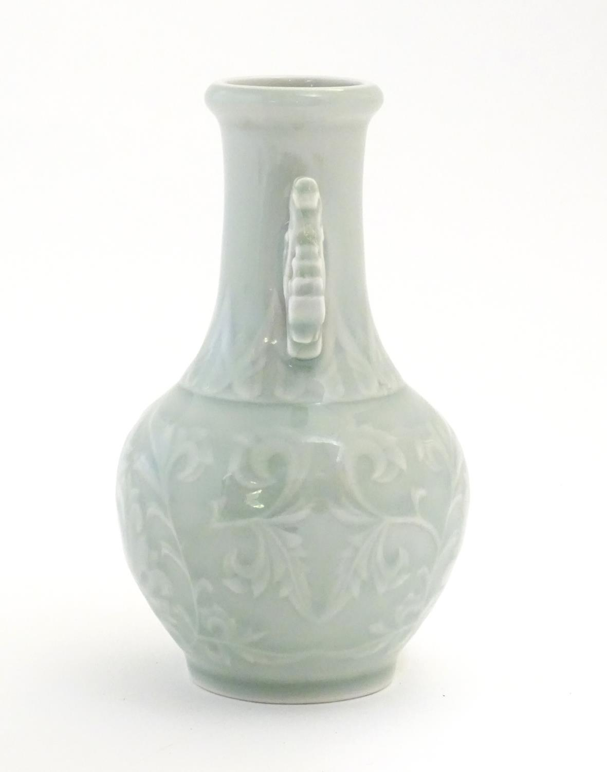 A Chinese celadon green baluster vase with twin handles and stylised foliate design. Approx. 6 1/ - Image 2 of 6