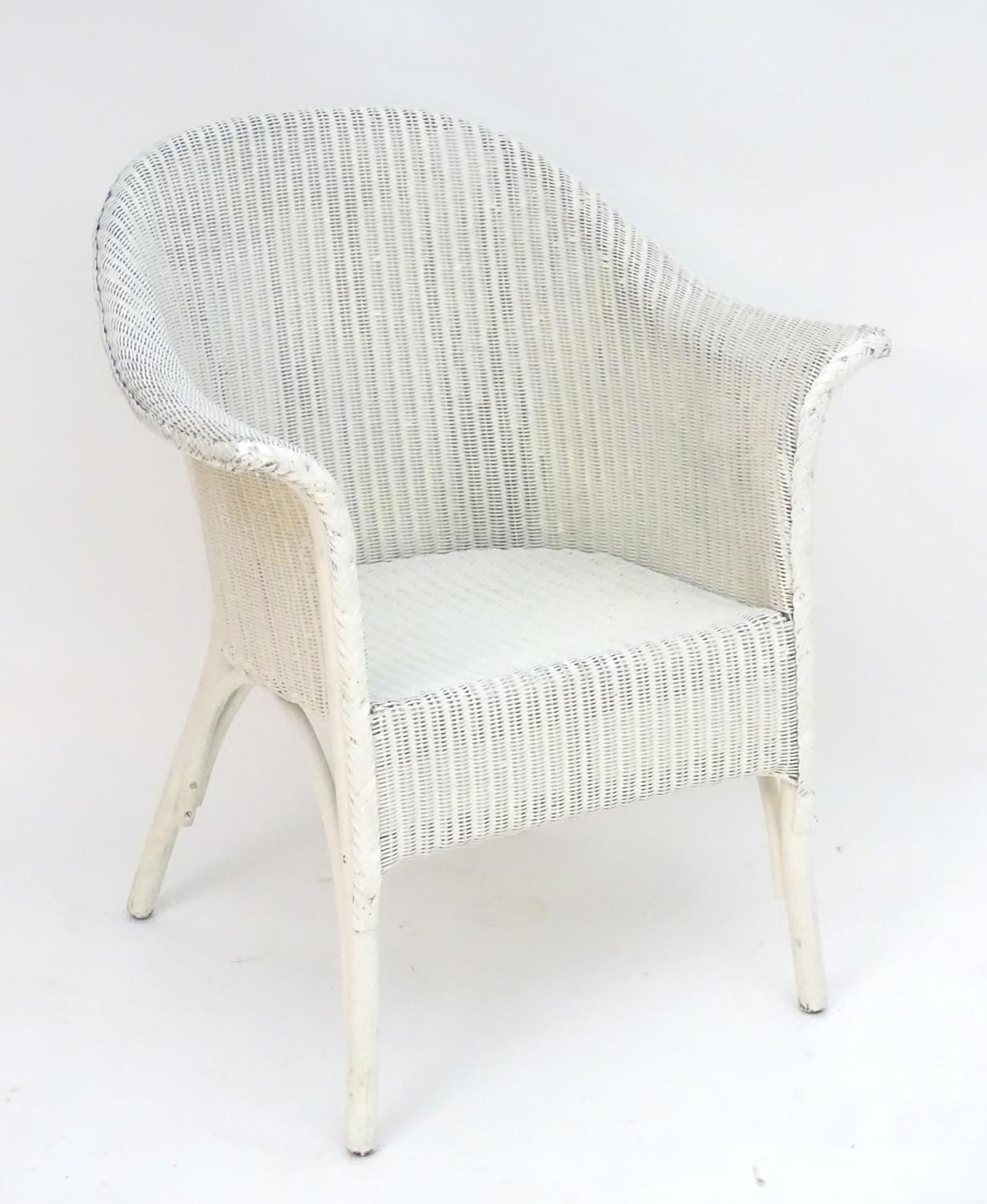 An early 20thC LLoyd loom armchair with a white painted bentwood frame. Bearing label to underneath.