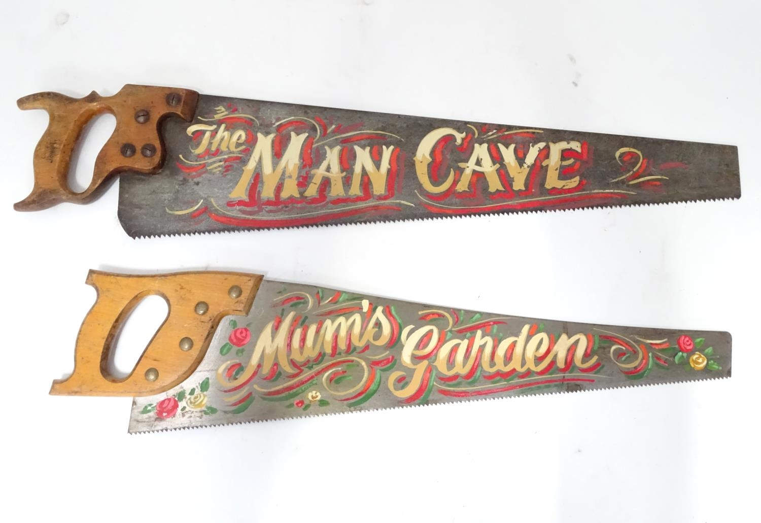 A pair of Spear and Jackson saws one with hand painted decoration ' The Man Cave ', the other with '