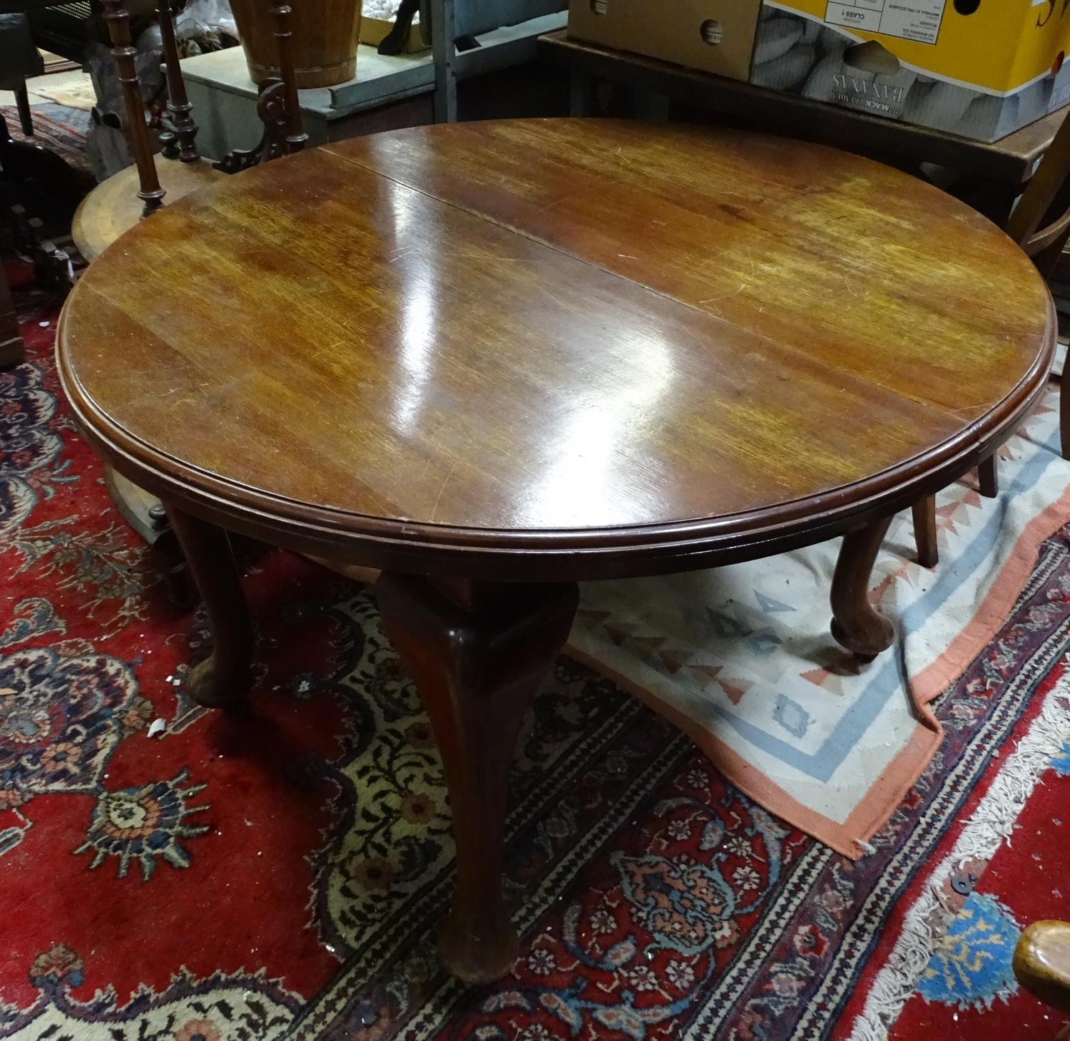 A mahogany oval dining table with cabriole legs and pad feet. Please Note - we do not make reference