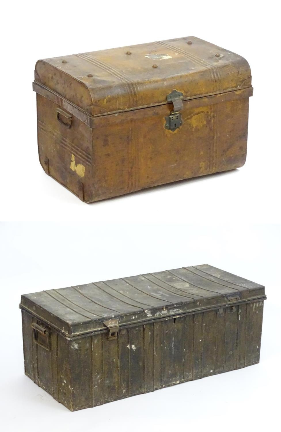Two late 19thC tin trunks with lifting lids and flanked by carrying handles. The largest measuring