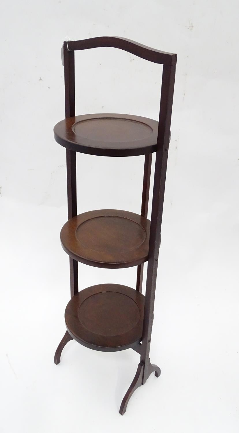 A mahogany folding cake stand with three tiers Please Note - we do not make reference to the