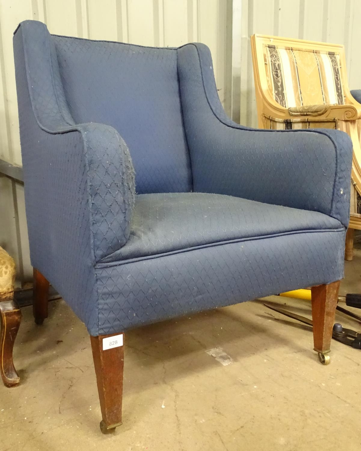 An early 20thC blue upholstered armchair Please Note - we do not make reference to the condition