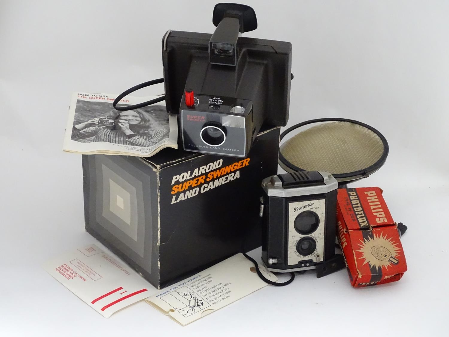 A boxed Polaroid camera, together with a Kodak Brownie and assorted photographic equipment Please