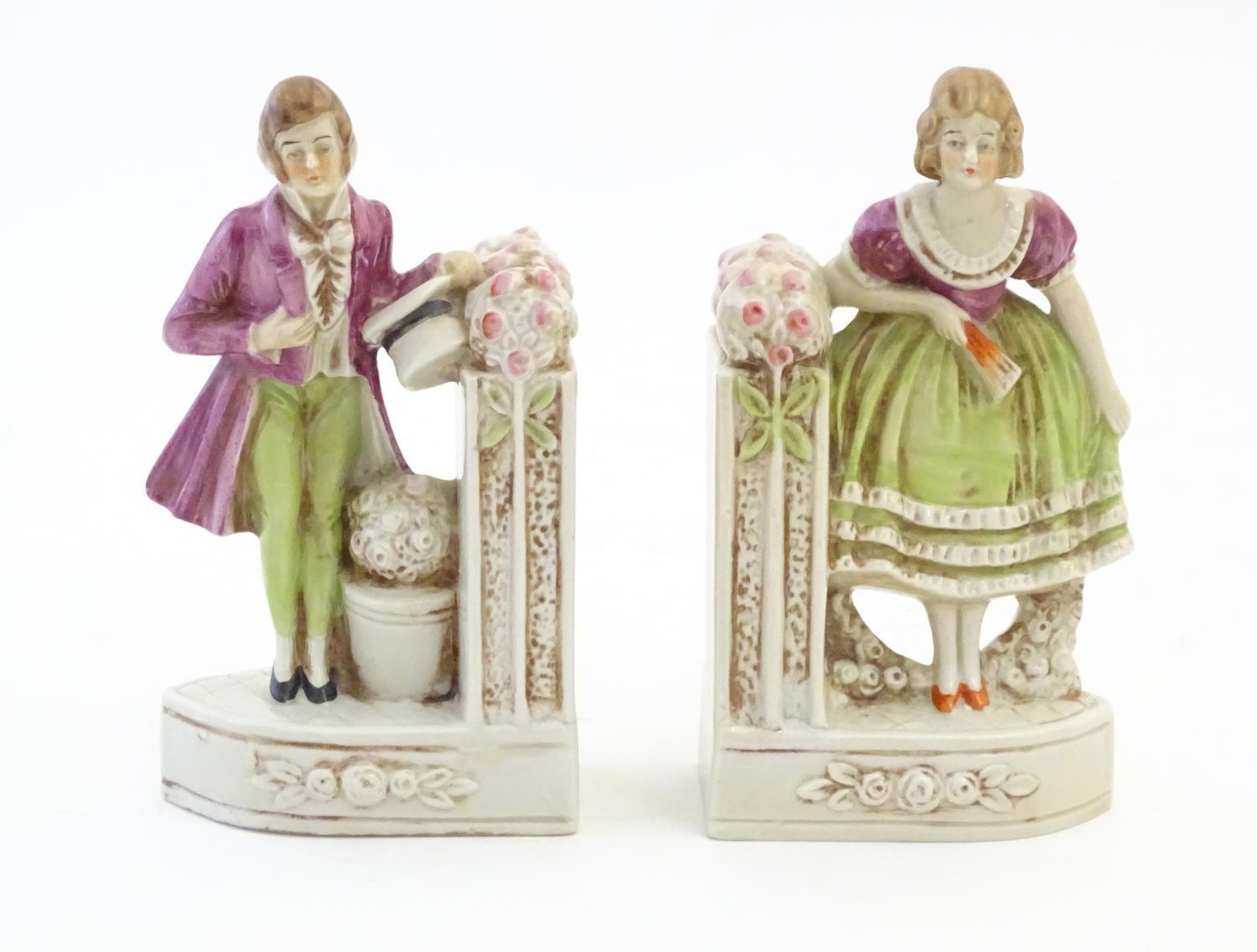 A pair of German porcelain figural bookends depicting a gentleman and a lady with flowers. Marked