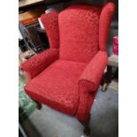 A red upholstered wingback armchair on ball and claw feet Please Note - we do not make reference