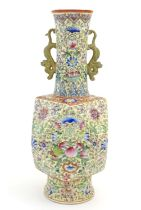 A Chinese famille jaune vase with twin handles modelled as stylised dragons, the body decorated with