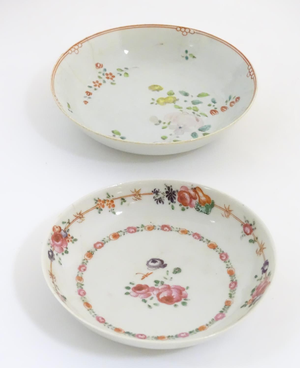 A New Hall style saucer with hand painted floral and foliate detail. Together with another.