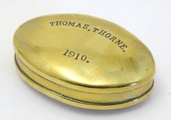 A Welsh early 20th century brass snuff box of oval form the lid engraved Thomas Thorne 1910, stamped