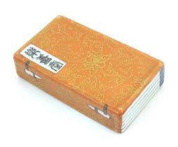 A Chinese porcelain model of a book with scrolling gilt foliate detail and character marks.