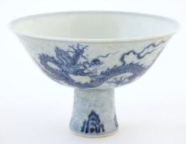 A Chinese blue and white dragon stem bowl with a raised foot. The bowl decorated with two dragons