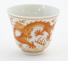 A Chinese wine cup with dragon detail and stylised flaming pearls and clouds. Character marks under.