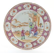 A Chinese famille rose plate depicting figures on a garden terrace with a mountainous landscape