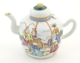 A Chinese famille rose teapot depicting scholars with attendants on a terrace with a mountainous