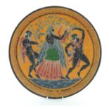 A terracotta charger decorated with a Classical Greek scene depicting Dionysus playing a lyre,