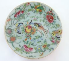 A Chinese celadon style plate decorated with bird, flower and butterfly detail. Character marks