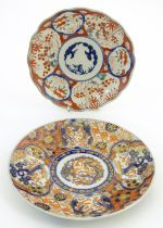 Two Oriental plates, one decorated with panelled detail depicting landscape scenes. The other