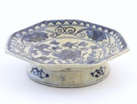 An Oriental blue and white footed dish, the octagonal top decorated with floral and foliate