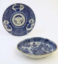 An Oriental blue and white plate with stylised peony detail, and stylised scrolling flower motifs to