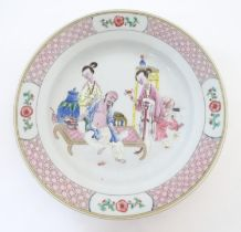 A Chinese famille rose plate decorated with an interior scene with an elderly scholar on a day bed