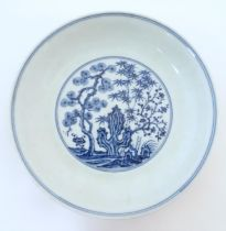 A Chinese blue and white dish with blossoming trees and stylised cactus detail. Character marks
