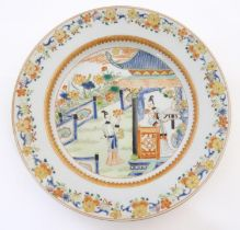 A Chinese plate depicting two ladies in a garden terrace with flowers, foliate, vases, etc.